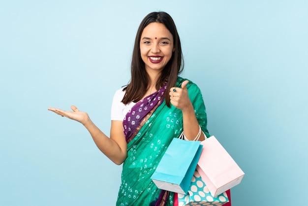 広告を挿入する手のひらに架空のcopyspaceを保持しているショッピングバッグを持つ若いインド人女性と親指
