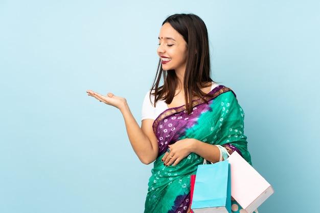 広告を挿入するために手のひらに架空のcopyspaceを保持している買い物袋を持つ若いインド人女性