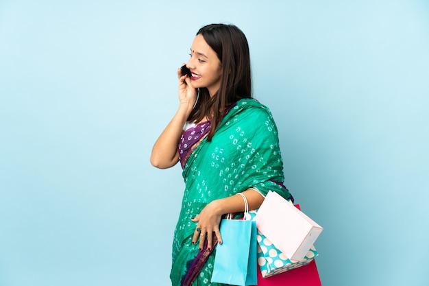 誰かと携帯電話との会話を続ける買い物袋を持つ若いインド人女性