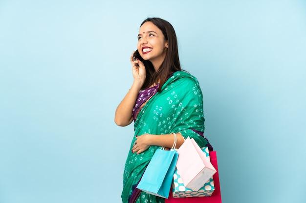 携帯電話との会話を維持する買い物袋を持つ若いインド人女性