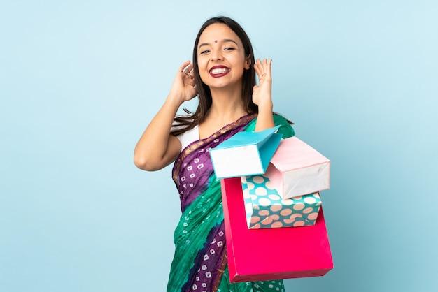 笑って買い物袋を持つ若いインド人女性