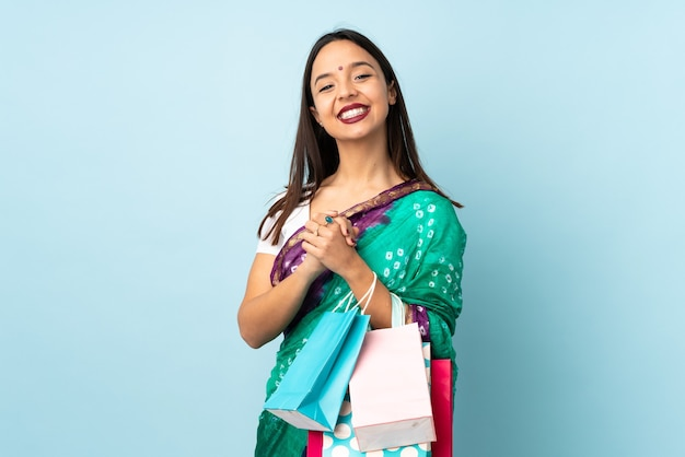 笑っている買い物袋を持つ若いインドの女性