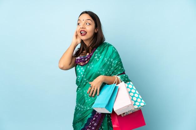 쇼핑 가방 귀에 손을 넣어 뭔가를 듣고 젊은 인도 여자
