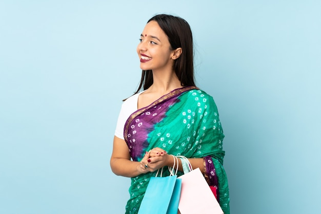 横に見える買い物袋を持つ若いインドの女性