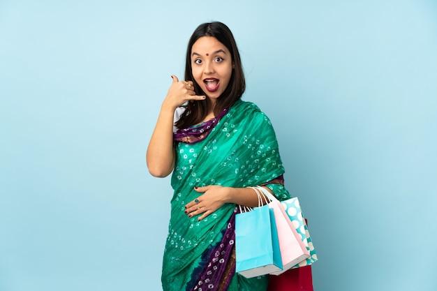 電話のジェスチャーを作る買い物袋を持つ若いインド人女性。