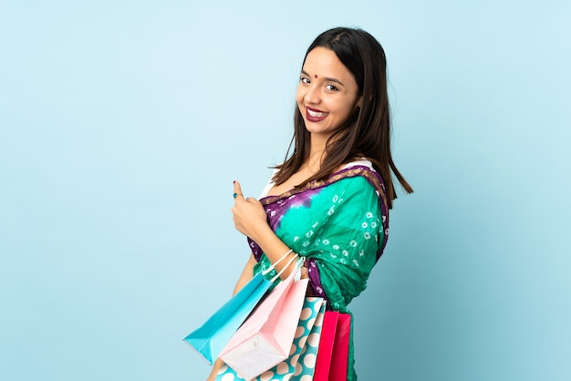 쇼핑백을 다시 가리키는 젊은 인도 여자