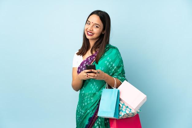 携帯電話でメッセージを送信する買い物袋を持つ若いインド人女性