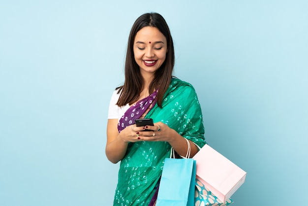 Young indian woman with shopping bags sending a message with the mobile