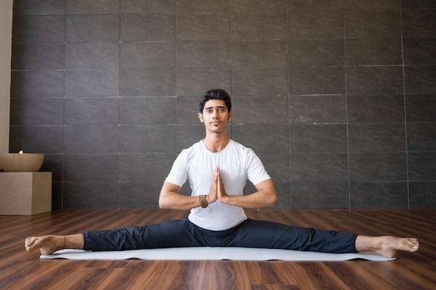 Young indian yogi doing splits in gym