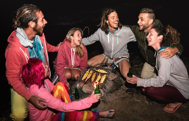 Young indie friends having fun together at night beach party cooking cobs at campfire - friendship travel concept with alternative people travelers drinking beer at summer bonfire - high iso image