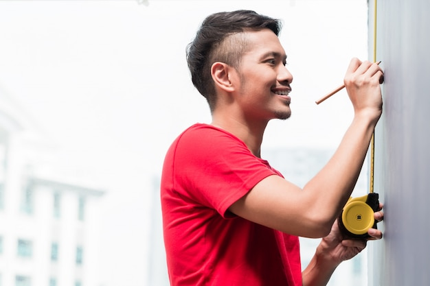Young indonesian man sizing with tape measure