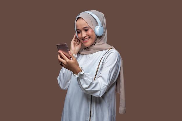 目を閉じながらワイヤレスヘッドフォンを使用して音楽を聴いているヒジャーブの若いインドネシアの女性