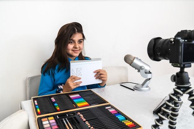 Молодой влиятельный человек и блогер ведет прямую трансляцию урока рисования карандашом из своей гостиной, смеется, смотрит в камеру и говорит в микрофон на видео или в социальной сети.