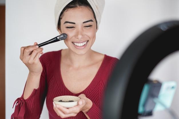 彼女のソーシャルメディアのフォロワーに黒の美容フェイスマスクの使い方を示す若いインフルエンサーの女性