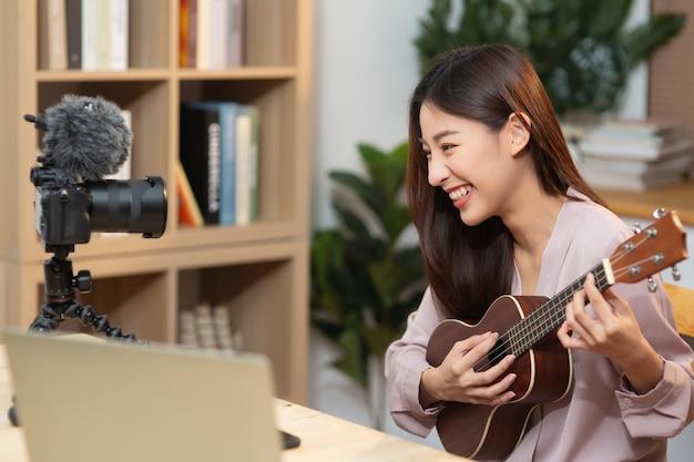 젊은 여성은 카메라로 촬영하여 녹음하는 동안 기타를 연주하고 가르치는 데 영향을 줍니다.