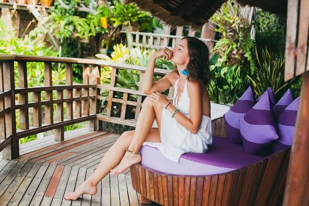 Молодая невинная чистая красивая женщина мечтает, сидя на диване в белом платье, романтичная, лирическая, думающая, зеленая тропическая природа, лето, расслабленная, расслабленная, ноги, курортный отель