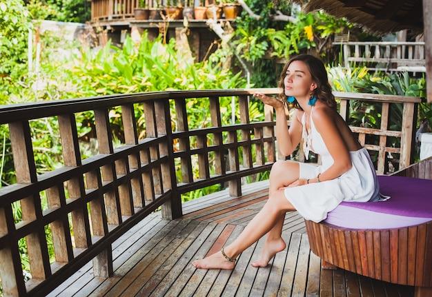 夢を見て、白いドレスを着てソファに座って、ロマンチックな、叙情的な、思考、緑の熱帯の自然、夏、リラックスした、寒い、足、リゾートホテルを夢見て、若い無実の純粋な美しい女性