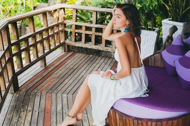 Giovane innocente pura bella donna che sogna, seduto al divano in abito bianco, romantico, lirico, pensiero, verde natura tropicale, estate, rilassato, agghiacciante, gambe, hotel resort