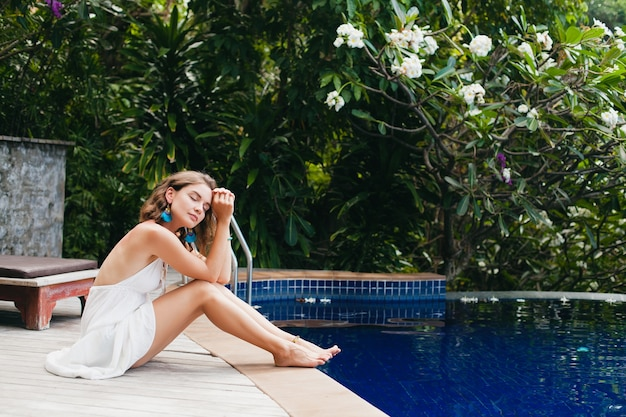 Young innocent pure beautiful woman dreaming, sitting at pool in white dress, romantic, lyrical, thinking, green tropical nature, summer, relaxed, chilling, long legs