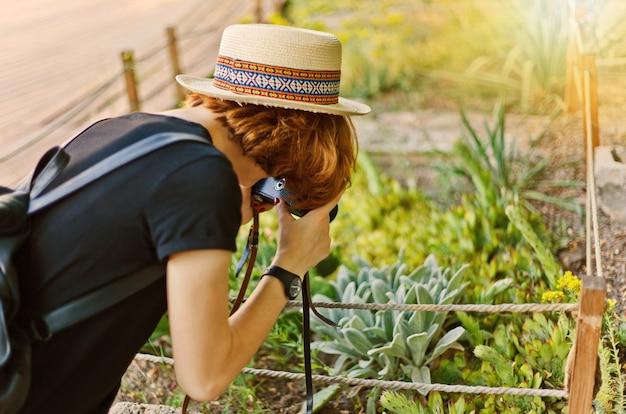 若い好奇心旺盛な女性観光客が屋外の庭でエキゾチックな植物を撮影
