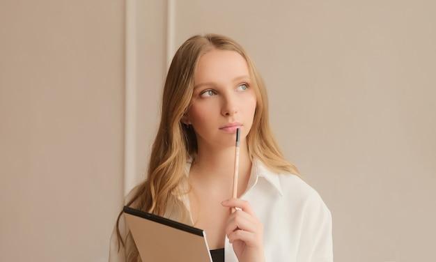 Молодая вдохновленная женщина задумчиво думает и делает заметки в бумажном блокноте