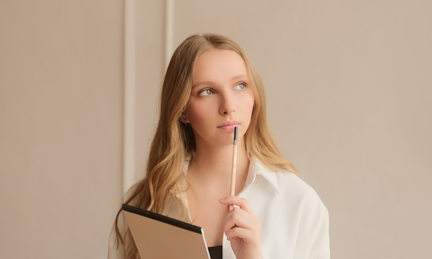 Young inspired woman pensively thinks and making notes in paper notebook Premium Photo