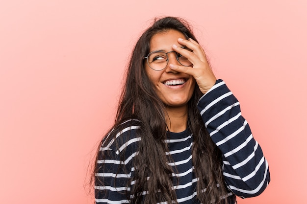 Young intellectual indian woman blink at the camera through fingers, embarrassed covering face.