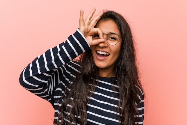 Young intellectual indian woman excited keeping ok gesture on eye.