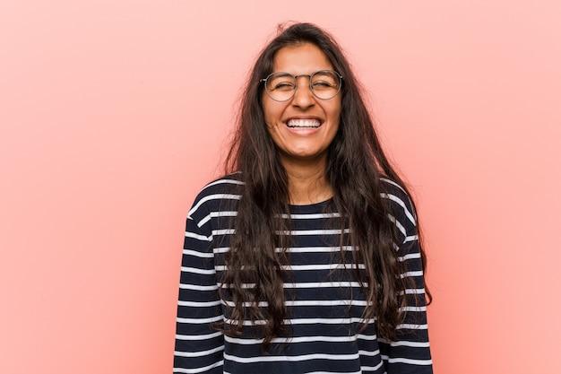 Молодая интеллектуальная индийская женщина смеется и закрывает глаза, чувствует себя расслабленной и счастливой.