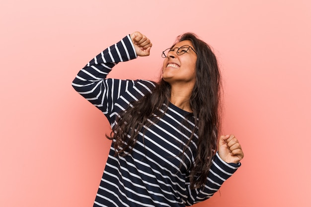 Young intellectual indian woman raising fist after a victory, winner concept.