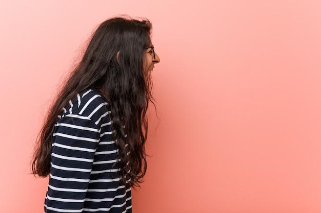 Young intellectual indian woman shoutingwards a copyspace