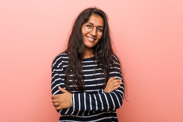 自信を持って、決意を持って腕を組んでいる若い知的インド人女性。