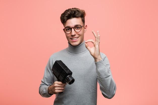 陽気で自信を持ってokのしぐさを示すフィルムカメラを保持している若い知的な男。