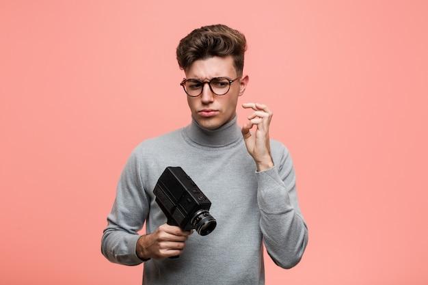 Молодой интеллектуальный человек, держащий пленочный фотоаппарат, скрестив пальцы за удачу