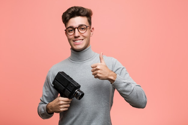 Young intellectual man holding a film camera smiling and raising thumb up