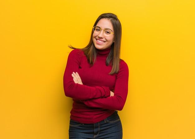 Молодая интеллектуальная женщина скрещивая руки, улыбаясь и расслабленной