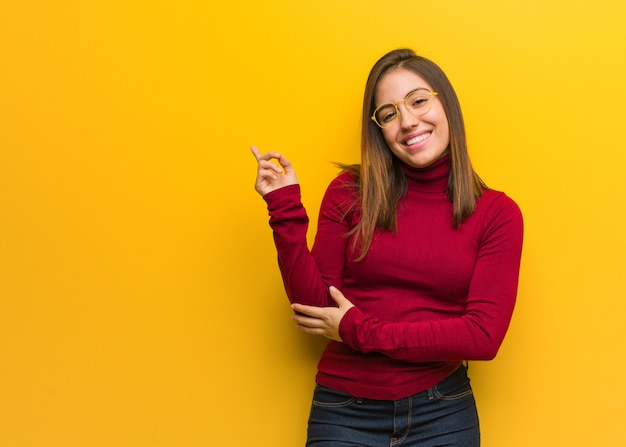 Young intellectual woman pointing to the side with finger