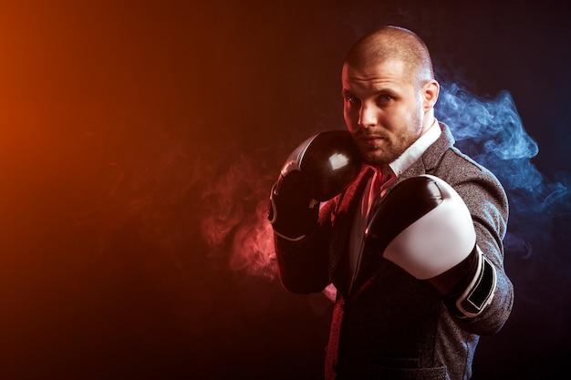 빨간색과 파란색 연기의 벽에 흰색 권투 장갑 상자에 젊은 지능형 남자