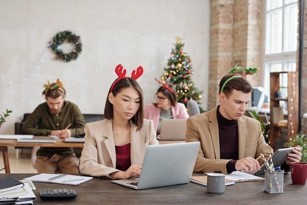 スマートカジュアルウェアとクリスマスヘッドバンドの若い異文化間同僚が列に並んでいる間、ラップトップの前でネットワーキング