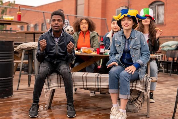 Молодая межкультурная пара футбольных фанатов и их друзей сидит в летнем кафе, пьет пиво с закусками и смотрит трансляцию матча