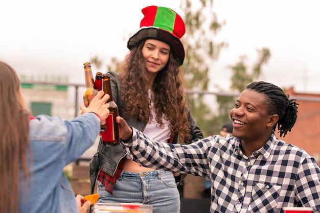 サッカーチームの勝利のために乾杯しながらビールのボトルとチャリンと音を立てる若い異文化ファン
