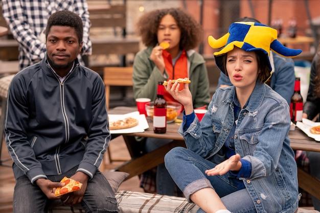 Молодые фанаты межкультурного футбола смотрят трансляцию в летнем кафе, пока один из них комментирует матч