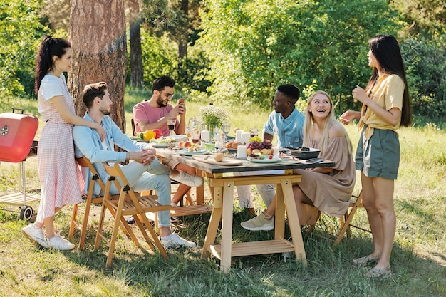 Young intercultural relaxed friends chatting by served table while spending time under pine tree in natural environment on summer day