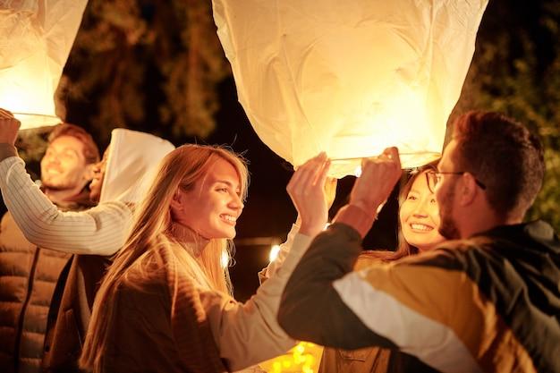 Молодые межкультурные улыбающиеся друзья держат большие белые воздушные шары с подсветкой, наслаждаясь ночной вечеринкой в естественной среде