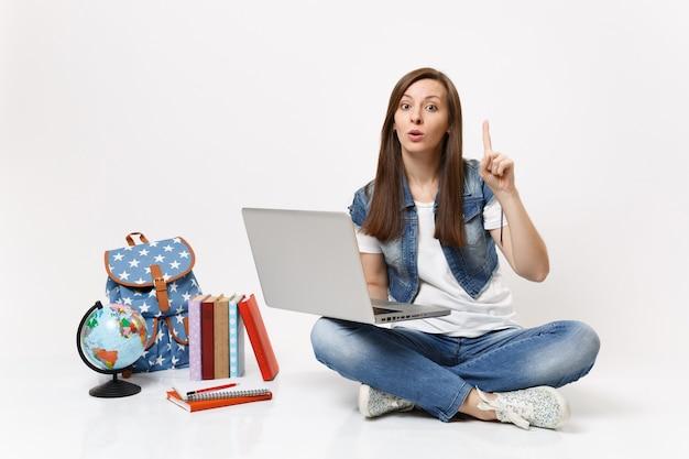 Giovane studentessa interessata che tiene in mano un computer portatile che punta il dito indice in alto seduto vicino al globo, zaino, libri scolastici isolati