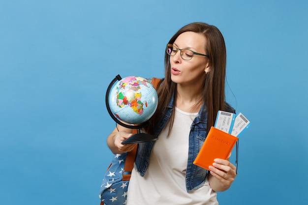 Молодой заинтересованный студент женщина в очках, глядя на перчатку мира, холдинг паспорт, билеты на посадочный талон, изолированные на синем фоне. обучение в вузе за рубежом. концепция полета авиаперелета.