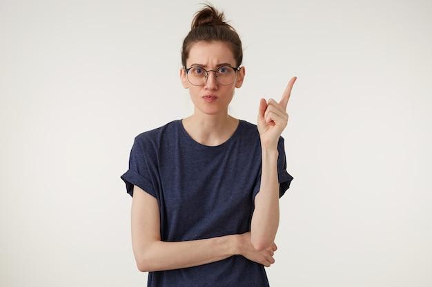 Молодая интересная женщина смотрит в очки, показывает указательным пальцем руки вверх