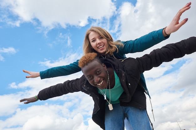 Young international couple on sky background. african guy and caucasian woman