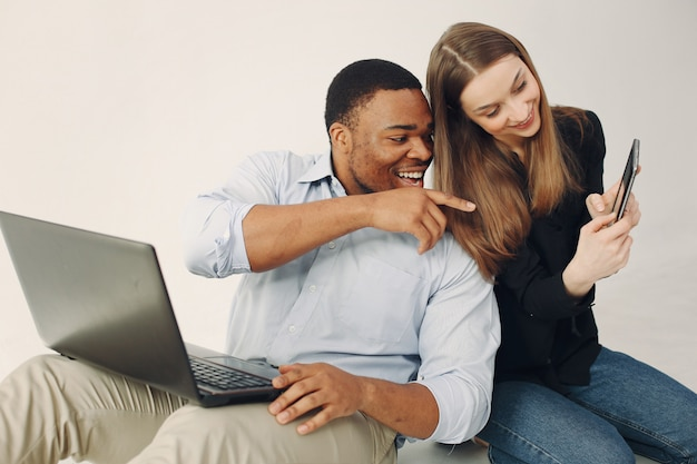 Young international couple working together and use the laptop