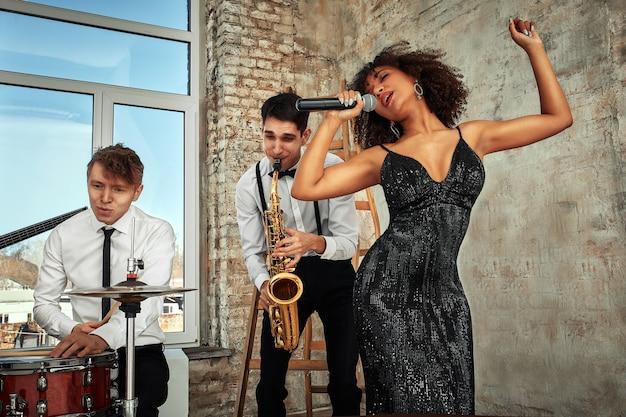 Молодые иностранные музыканты, группа, выступающая на сцене лофта